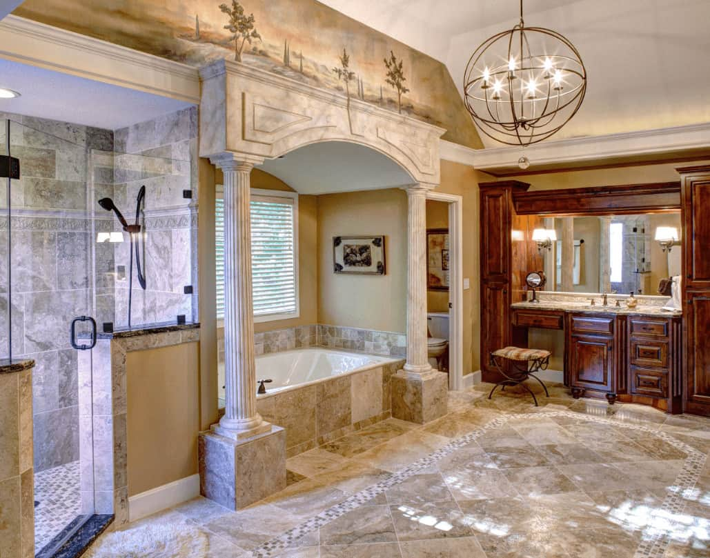 A spherical chandelier illuminates this master bathroom boasting a wooden sink vanity and alcove tub designed with landscape mural on top.