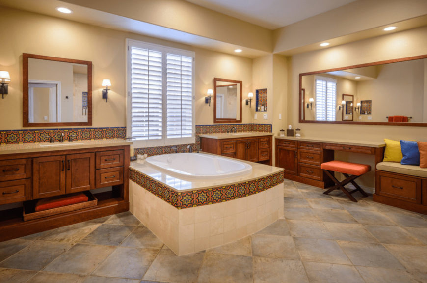 The Mediterranean master bathroom features a deep soaking tub and wooden vanities lined with eye-catching decorative tiles. There's a built-in seat on the side topped with beige cushion and multi-colored pillows.