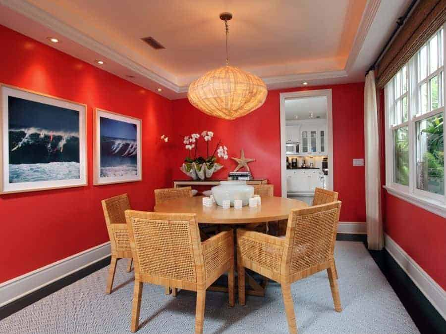 The white tray ceiling has a warm yellow glow to its borders that is augmented by the pendant light with a rustic hood that matches the dining chairs that have woven wicker designs. All of these are contrasted by the bright red walls accented with framed photos of surfers riding a large wave.