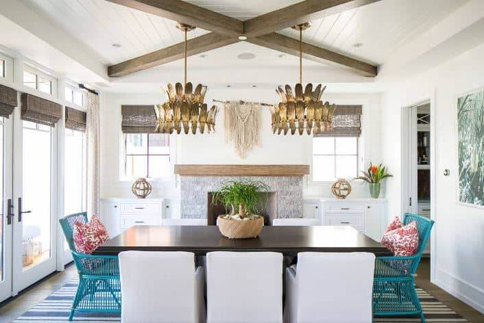 The bright white ceiling is complemented by two exposed wooden beams in a cross design. There is also a pair of decorative pendant lights with leaf designs hanging over the dark wooden dining table that has two kinds of dining chairs. There are two rustic green bamboo chairs and armchairs with white slipcovers.