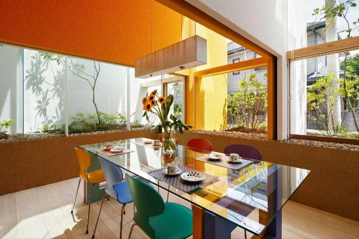 This informal dining room has modern chairs of different colors that complement the modern glass-top dining table. This is surrounded by tall glass windows with plant boxes that have plants just outside the glass for that unique tone to pair the orange and brown textured walls.