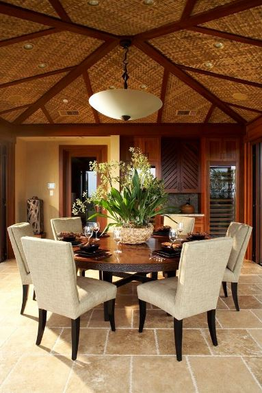 The arched ceiling of this Tropical-style dining room has woven wicker on it with exposed wooden planks to hold it. In the middle point of it hangs a white dome pendant light that matches the dining chairs with beige cushions and dark legs.