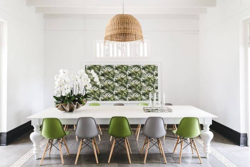 The brown rustic basket hood of the dome pendant light stands out against the white ceiling with exposed wooden beams and white walls as well as the white dining table. These are contrasted by the green elements of the modern dining chairs and the framed artwork of leaves paired with a potted plant in a large shell.
