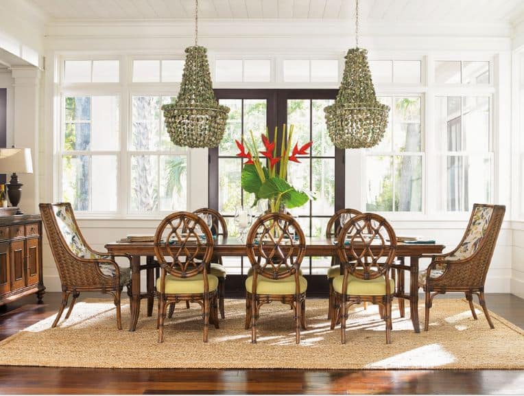 This dining set has a pair of high-backed bamboo chair on each end of the rectangular wooden dining table. These are different form the other dining chairs that are also made of bamboo but has oval backs and beige seat cushions. These are topped with a couple of decorative pendant lights made of shells.
