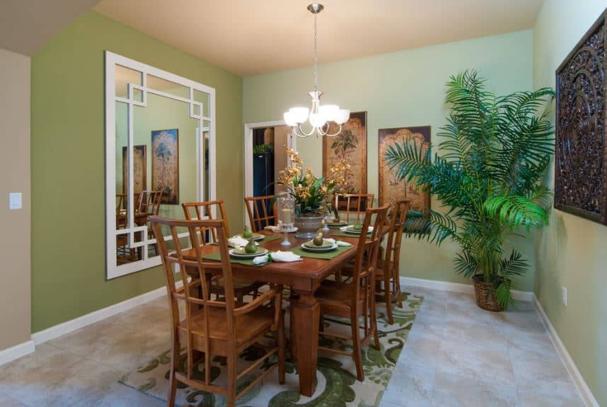 The avocado walls of this small dining room matches well with the green patterned area rug underneath the wooden table and its chairs. This is also complemented by the potted plant on the corner beside the apir of wall-mounted artworks.