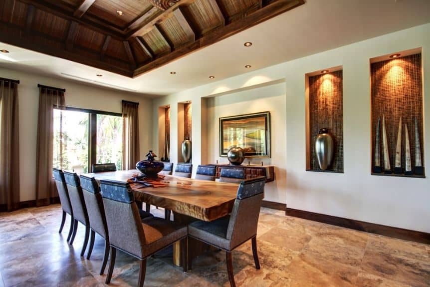 The earthy wooden ceiling is paired with contrasting white walls that have small alcoves on it for decor display that has recessed lights. The large rectangular dining table matches the marble flooring and the brown cushioned dining chairs surrounding it.