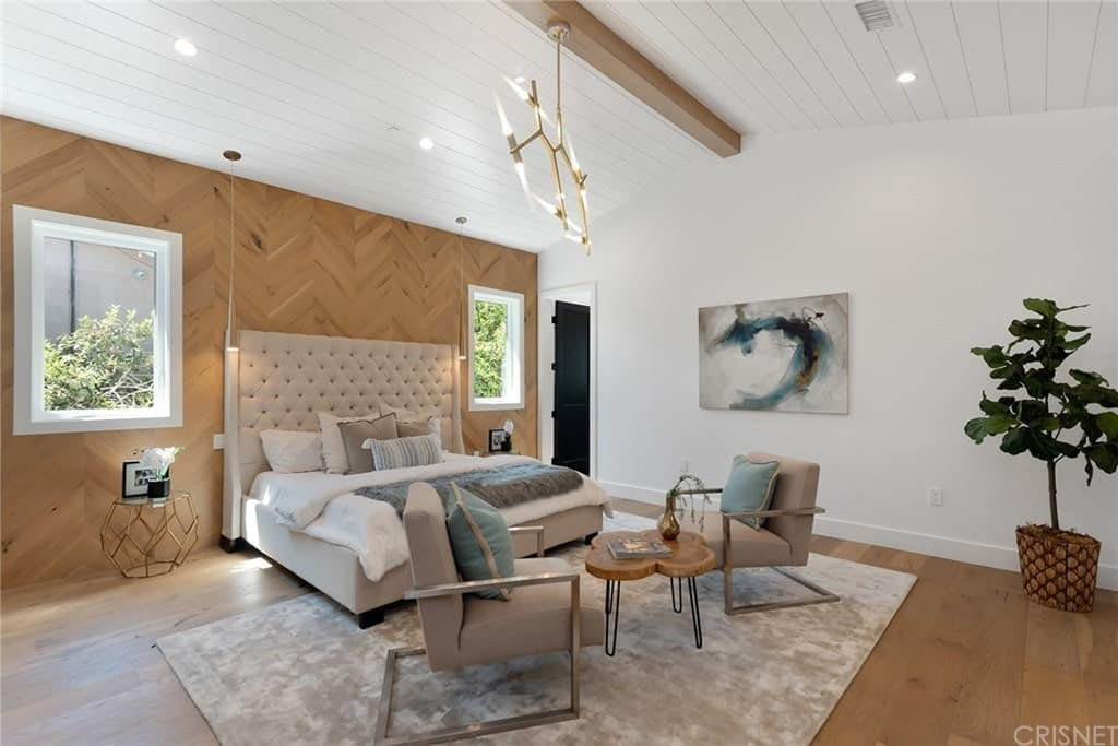 Master bedroom with pitched beam ceiling, an accent wall, stylish furniture, and a seating area above an area rug on hardwood flooring.