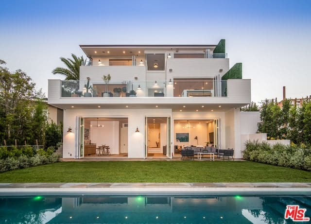 Beach Chic Farmhouse style home exterior facing the backyard with a private pool.
