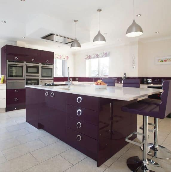 The dark purple hue that dominates this modern kitchen is almost nearing the black palette. This is a nice contrast to the white countertops, the light gray flooring tiles, light beige walls and white ceiling as well as the stainless steel appliances.
