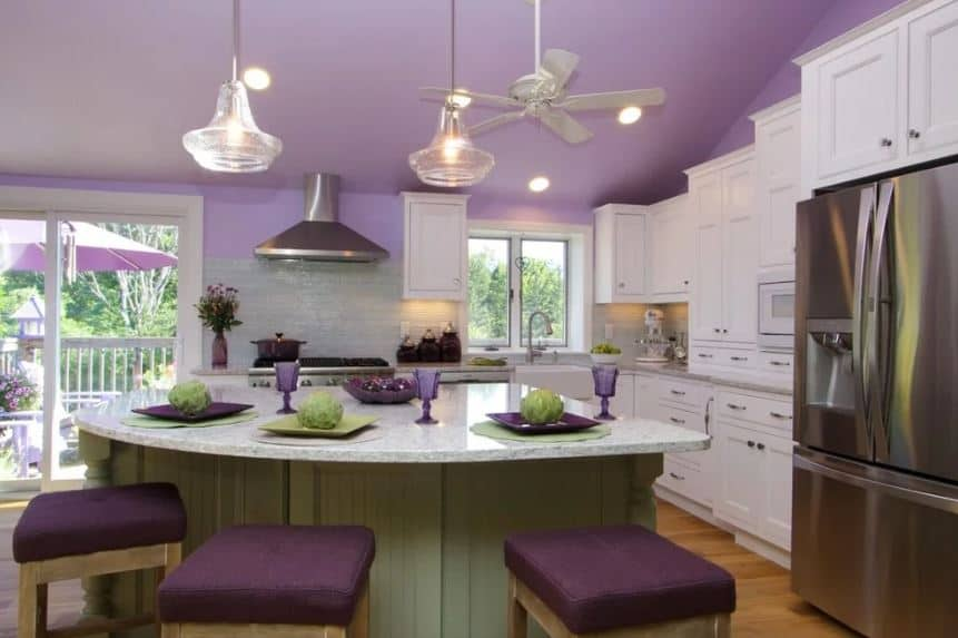 This homey and comfortable kitchen is dominated by the light purple shed ceiling and walls. This matches with the purple cushions of the wooden stools of the curved kitchen island. And it also puts emphasis on the white brightness of the shaker cabinets and drawers.