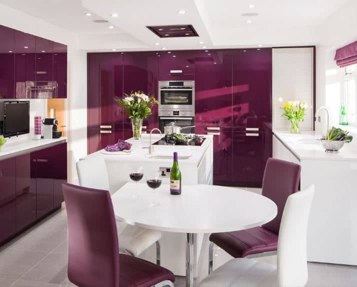 This kitchen has an informal dining area beside it that has a modern white round table and purple leather chairs. This matches well with the modern sleek cabinets of the kitchen that stands out against the white ceiling and counters.