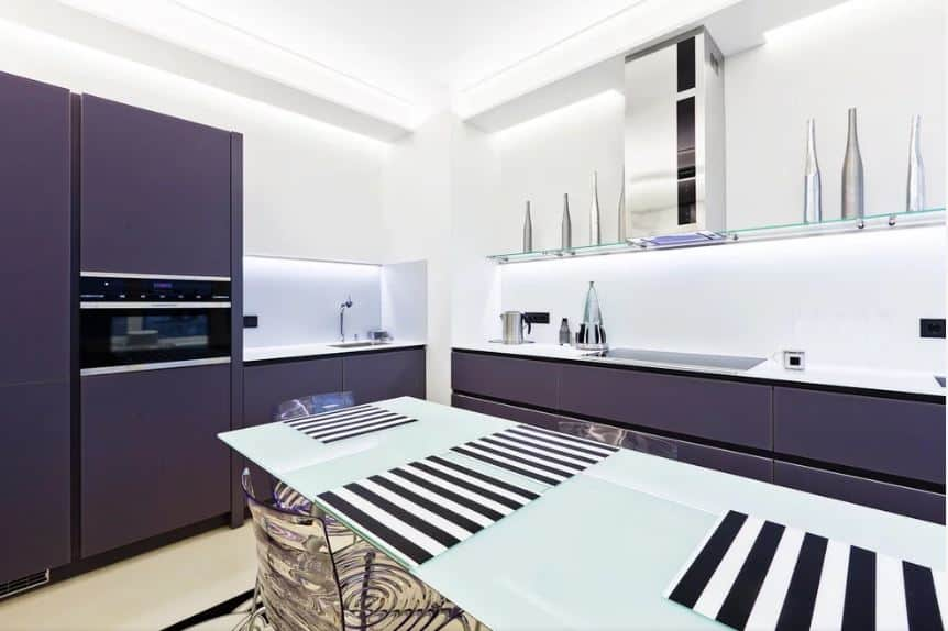 This modern and bright kitchen is dominated by two tones. The white ceiling matches with the white walls and countertops. This is countered by the dark purple matte cabinets of the L-shaped peninsula that also houses the oven.