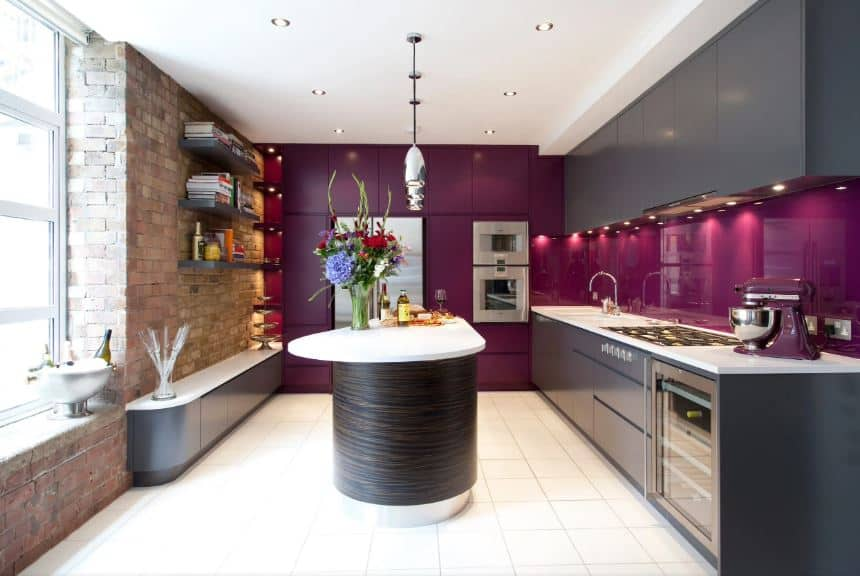 This kitchen is an eclectic fusion between modern and industrial-style. The red brick wall on one side has a window that brings in natural lights to the white ceiling and flooring tiles that is contrasted by modern dark gray cabinetry augmented by sleek dark purple walls and backsplash.