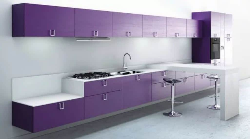 The wide light gray wall supports the large floating peninsula with purple cabinets and drawers extending to the cabinets above it connected through the housed fridge at the far end. In the middle of this is an attached white modern table to serve as a breakfast bar.