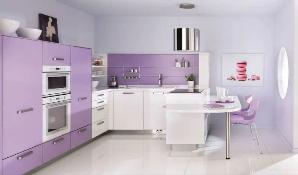 The U-shaped peninsula has a built-in white table on the side for an informal dining area paired with two light purple modern chairs that match with the light purple section of the peninsula that houses the oven.