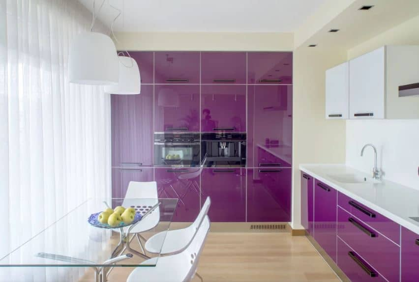 The modern kitchen is also a part of the dining room that has a glass-top table and modern white chairs that are illuminated by the large curtained windows. These also brighten up the sleek deep purple cabinetry that are embedded into the walls of the kitchen.