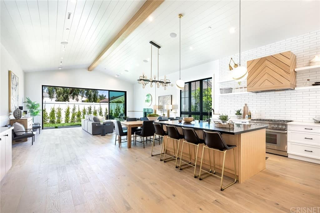 Modern farmhouse single-story home interior with open layout featuring pitched beam ceiling, wide plank French Oak floors, custom built-ins, and gourmet Chef's kitchen with stone counters, thermador appliances, and an Island with a large breakfast bar.