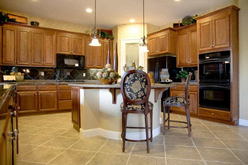 Black appliances complement the diamond pattern backsplash flanked by wooden cabinets. There's a granite top island in the middle accompanied by glass pendant lights and floral cushioned chairs.