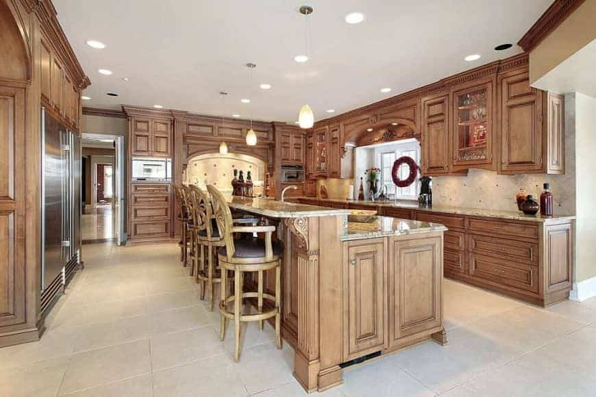Brown kitchen showcases stainless steel appliances and wooden cabinetry surrounding a matching island bar over beige tiled flooring. It is lined with round cushioned stools and glass pendant lights.
