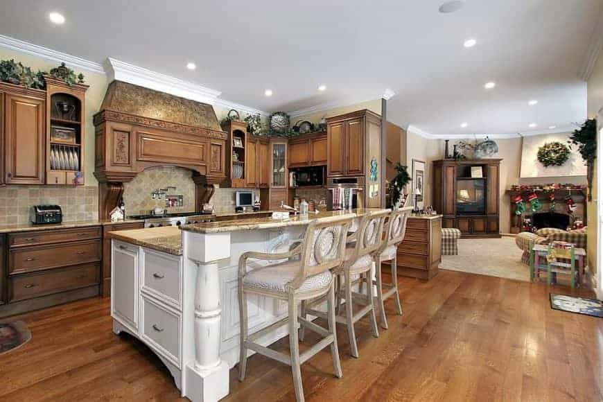 An open concept kitchen with tiled backsplash and wooden cabinetry blending in with the hardwood flooring. It includes a raised breakfast island that's paired with cushioned counter chairs.