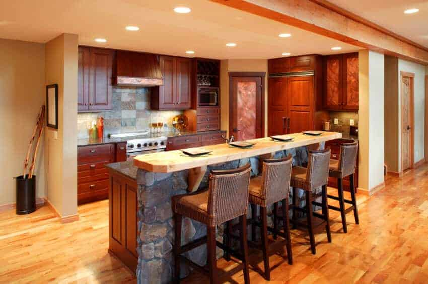 This kitchen features redwood cabinetry and a stone two-tier island paired with wicker counter chairs. It is illuminated by recessed lights mounted on the regular beige ceiling.