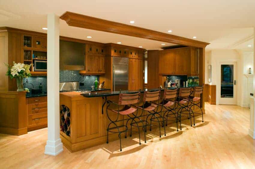 Brown kitchen with a white column and wooden cabinetry matching with the peninsula that's fitted with a built-in wine rack. It is lined with metal counter chairs over the light hardwood flooring.