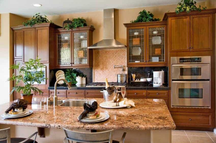 Green potted plants create a refreshing ambiance in this kitchen with wooden cabinetry and a beige breakfast island topped with granite counter and a dual sink.