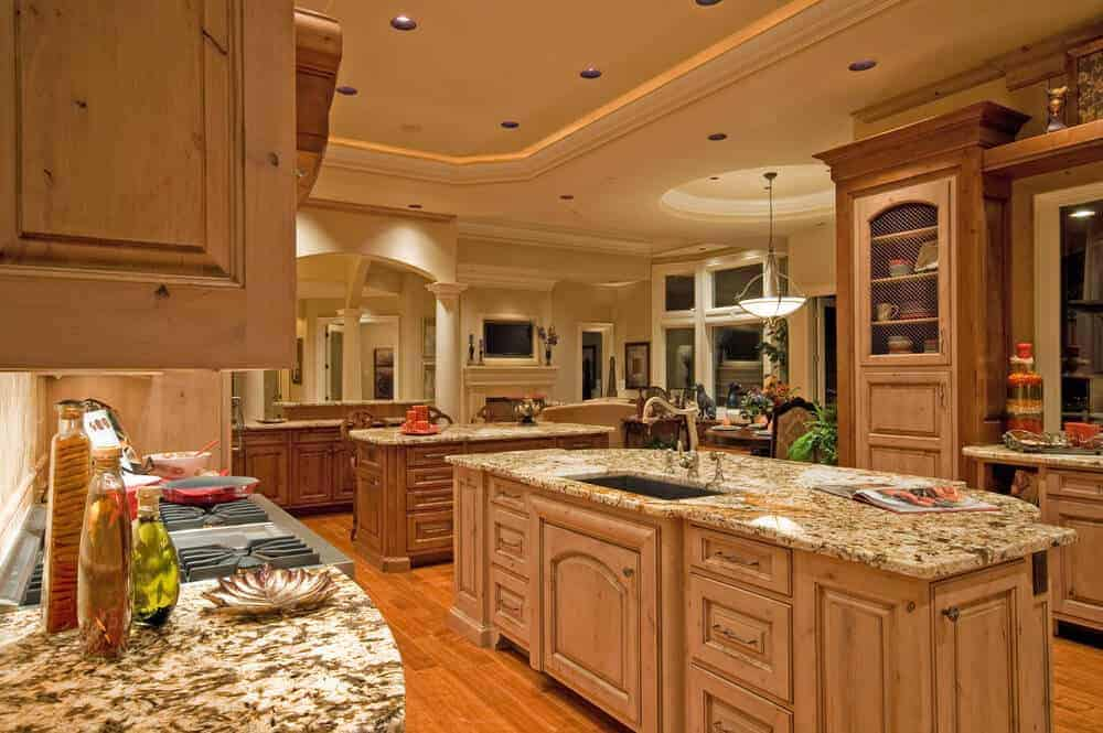 This kitchen offers granite countertops and two islands blending in with the cabinetry and hardwood flooring. It is illuminated by recessed lights mounted on the tray ceiling.