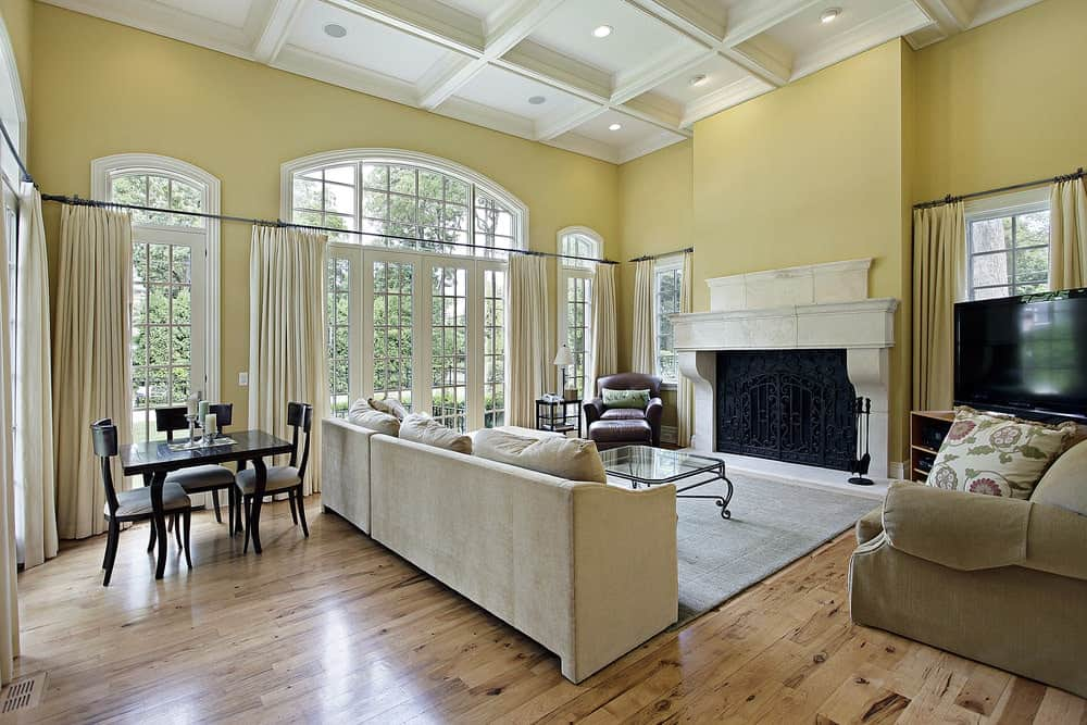 Fresh living room with wide plank flooring and white coffered ceiling mounted with recessed lights. It has cozy seats and a fireplace covered in an ornate wrought iron screen.
