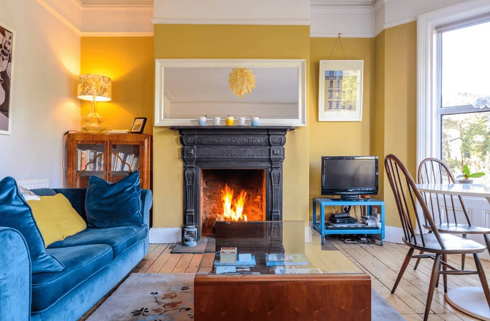 A blue velvet sofa stands out in this yellow living room with a glass top coffee table and white framed mirror mounted above the black fireplace.