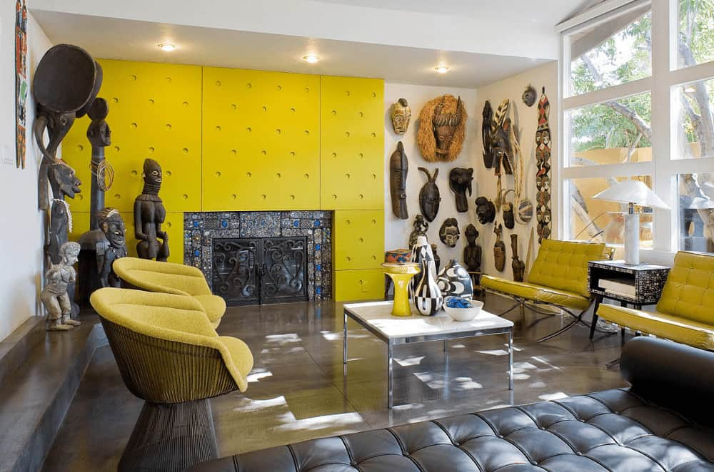This living room is decorated with masks and sculptures sitting next to the gorgeous fireplace. It has yellow chairs and a black tufted sofa paired with a metal coffee table.