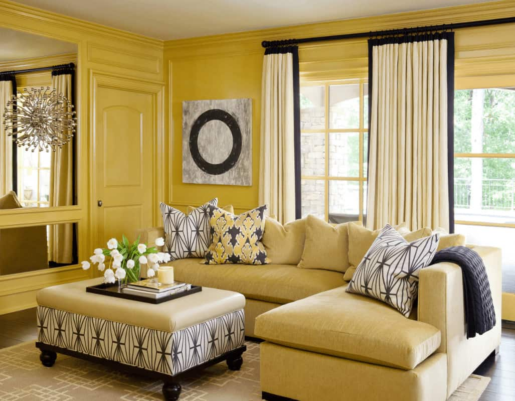 Patterned pillows and ottoman adds a striking accent in this yellow living room with wainscoted walls and dark hardwood flooring topped by a gray area rug.
