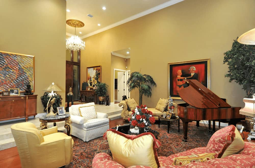 A classy living room filled with a baby grand piano and mismatched seats over the classic area rug. It has rich hardwood flooring and yellow walls mounted with gorgeous artworks.