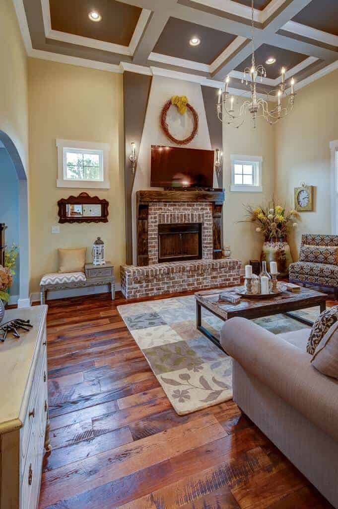 A candle chandelier illuminates this living room offering cozy seats and a brick fireplace framed with rustic mantel. It has a gray coffered ceiling and wide plank flooring topped by a floral checkered rug.