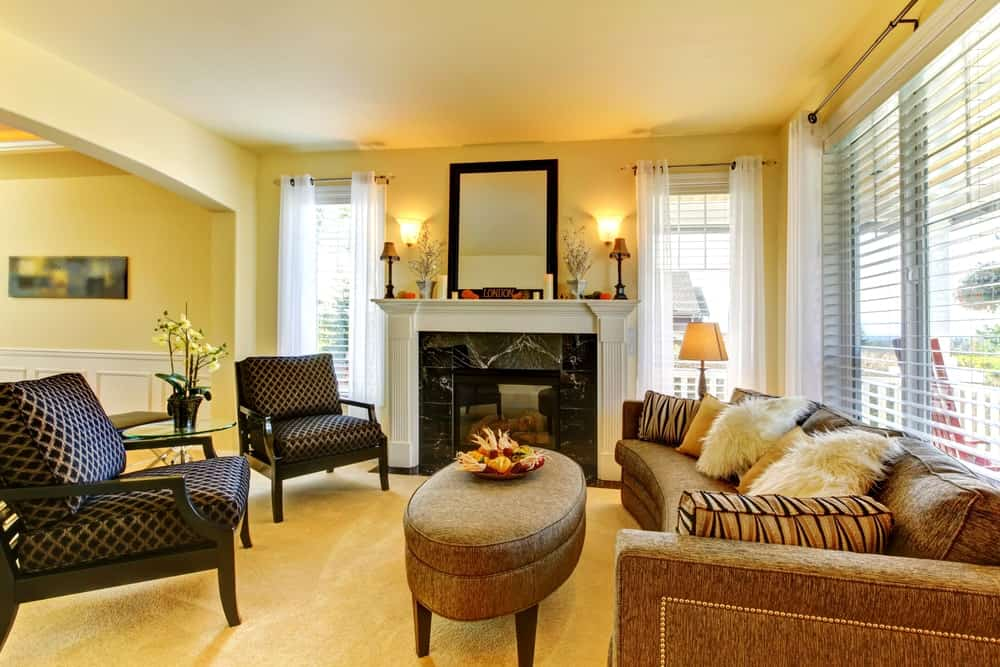 Patterned armchairs and a curved sofa filled with fluffy and furry pillows surround an oval ottoman that faces the fireplace with a black framed mirror on top lighted by wall sconces.