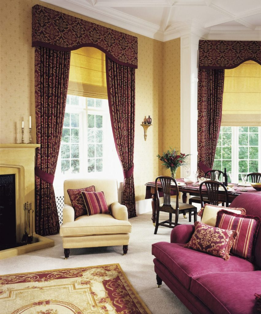 A plum sectional sofa complements the classy patterned draperies covering the white framed windows. This room has a beige armchair and a red printed rug that lays on the carpet flooring.