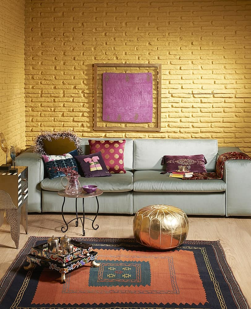 A wooden framed wall art mounted on the yellow brick wall hangs above the gray sofa filled with gorgeous pillows. It is accompanied by a metal coffee table and gold ottoman that sits on a bordered area rug.