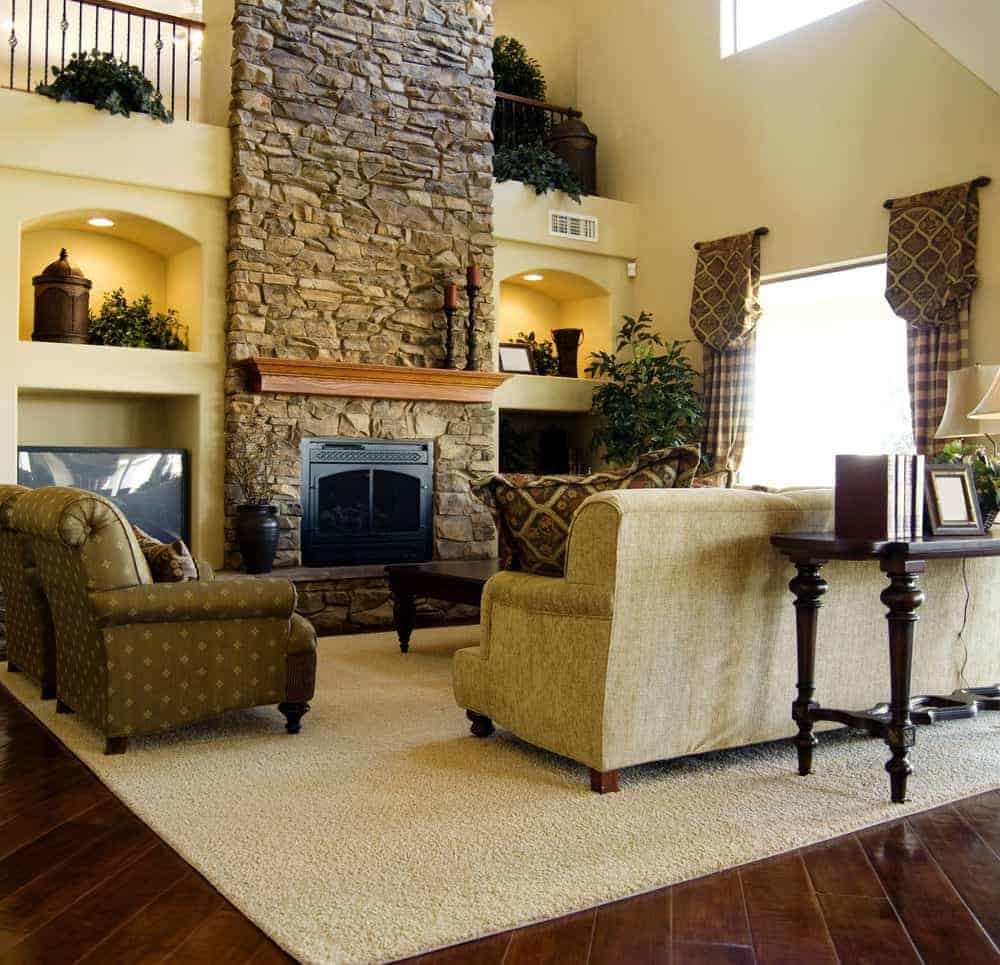 A stone brick fireplace adds texture in this living room with inset wall niches and wide plank flooring topped by a beige area rug. It includes comfy seats along with patterned and checkered draperies covering the picture window.