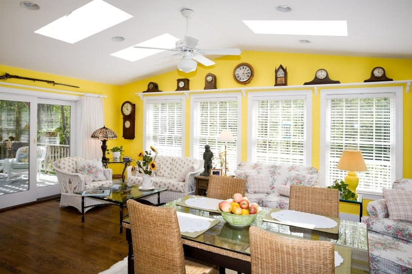 Various clocks and white framed windows fill the yellow wall in this living area with hardwood flooring and vaulted ceiling mounted with skylights and a fan.