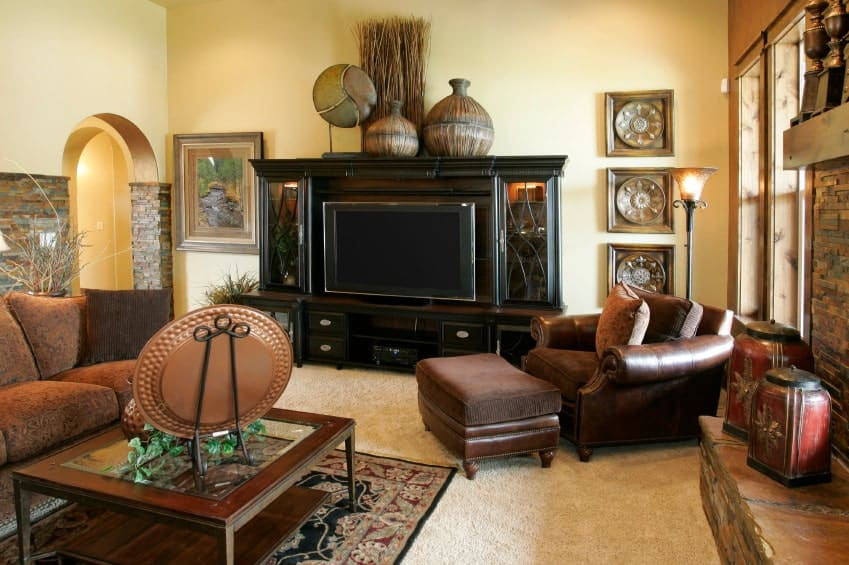 This living room features a brown leather lounge chair and sectional sofa paired with a wooden coffee table. It is decorated with antique wall arts and vases that sit on a dark wood cabinet.