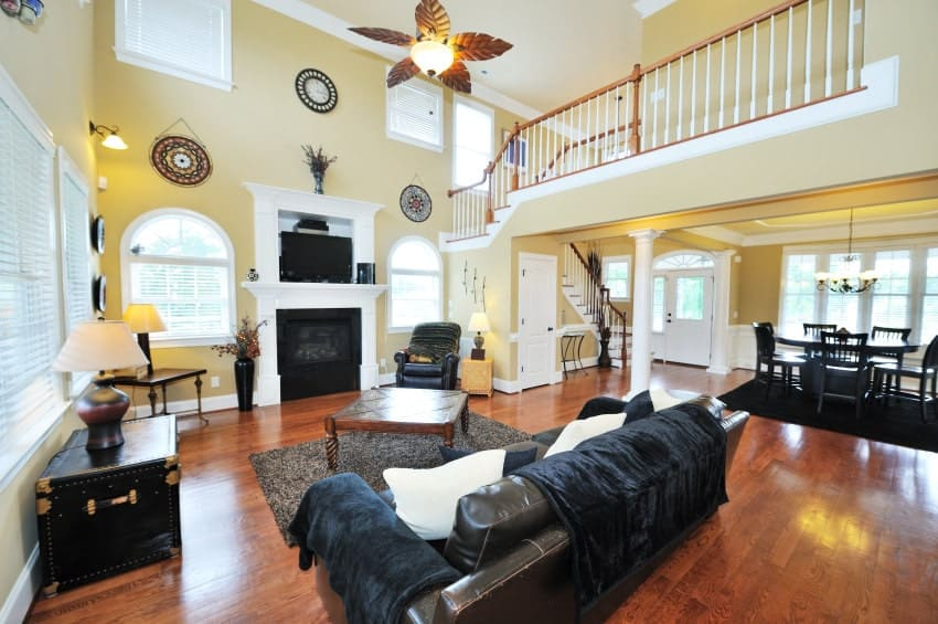 Spacious living area with high ceiling and rich hardwood flooring topped by a gray shaggy rug. It has black leather seats and a fireplace situated in between the arched windows.