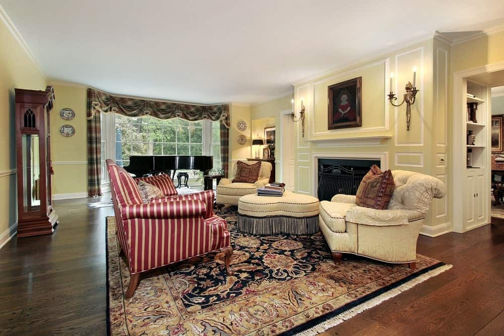 A red striped sofa over a tasseled area rug stands out in this yellow living room with comfy seats and ottoman that faces the fireplace accented with a lovely painting.