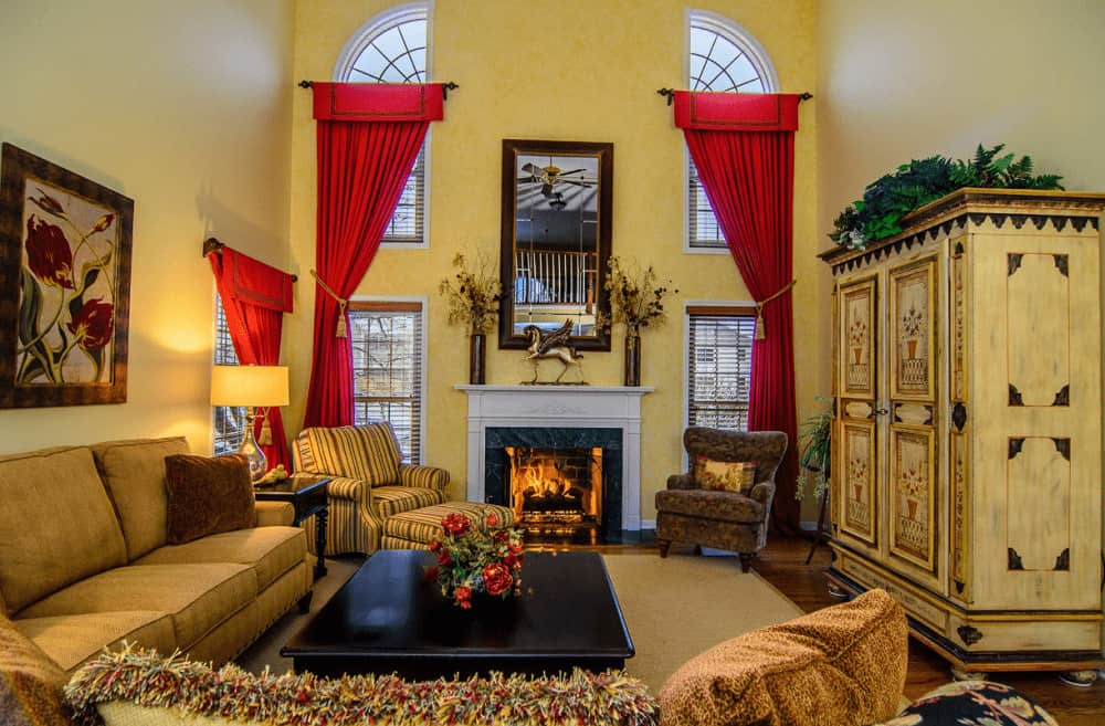 Classy red draperies covering the glazed windows stand out in this yellow living room with cozy seats and a fireplace topped with vases and horse sculpture.
