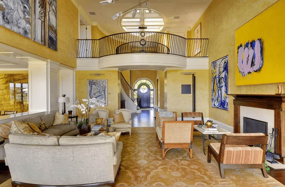 Yellow living room decorated with abstract paintings and a contemporary chandelier that hung from the high ceiling. It has plenty of seats and a glass enclosed fireplace framed with wooden mantel.