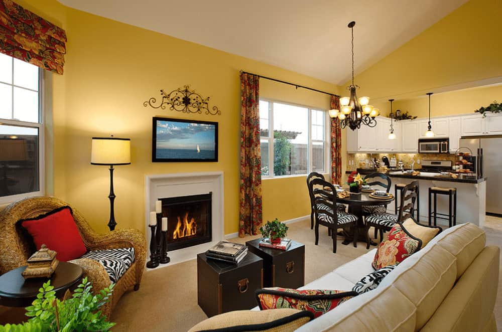 A modern fireplace faces the dark wood coffee tables and beige sectional sofa filled with fluffy pillows. It is accompanied by a wicker chair and a drum floor lamp.