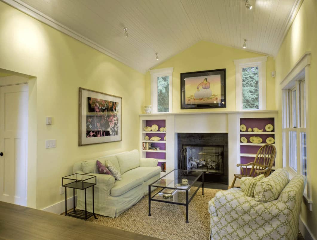Yellow living room with cozy seats and a glass enclosed fireplace flanked by purple shelvings. It is illuminated by chrome track lights mounted on the cathedral ceiling.