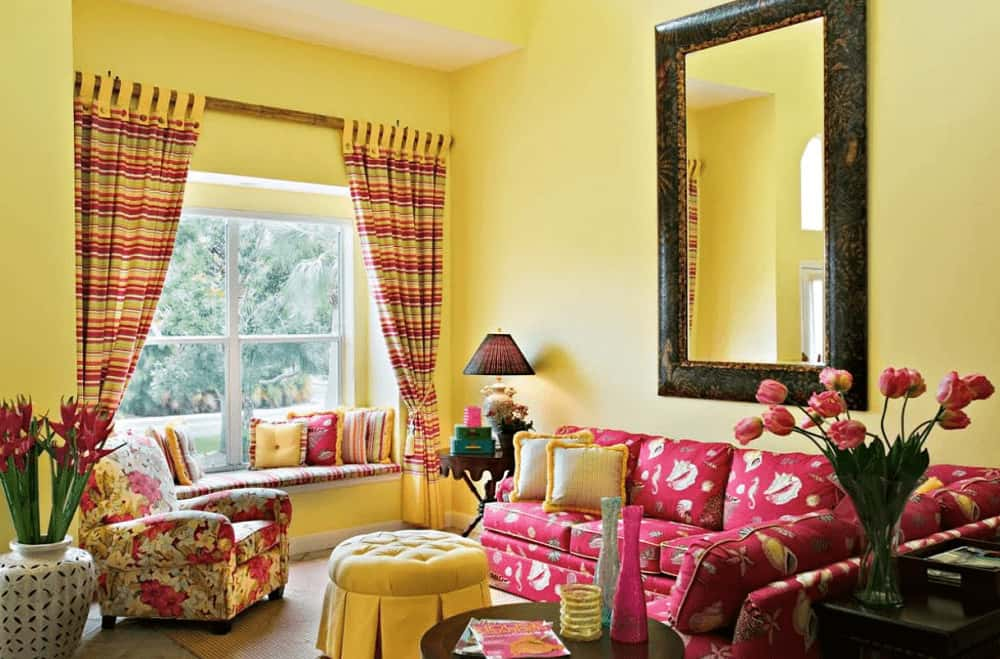 A large mirror hangs above the red sectional accompanied by a floral armchair and tufted round ottoman. There's a window seat nook on the side completed with small pillows and striped cushion that matches the draperies.