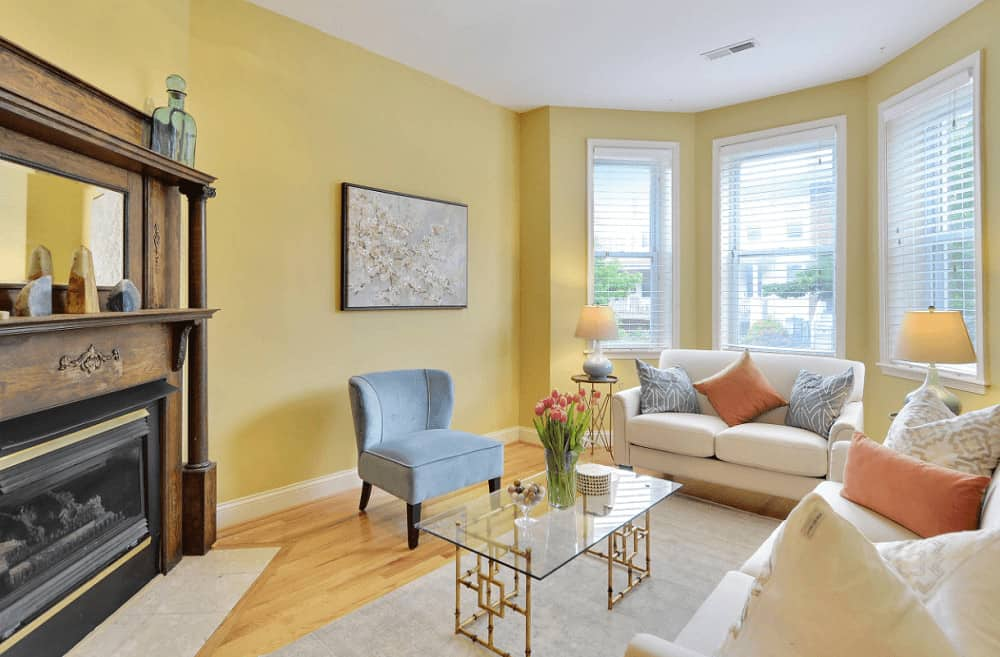 Bright living room with white sofas and a gray wingback chair paired with a stylish glass top coffee table. It includes lovely wall art and a corner fireplace with a mirror on top.