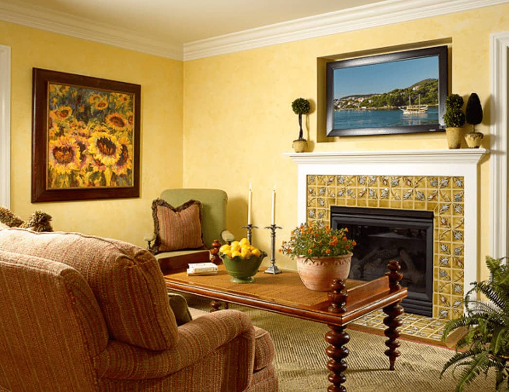 A flat-screen TV mounted on the inset wall hangs above the glass enclosed fireplace framed with decorative surround tiles and white mantel. This room has comfy seats and a wooden coffee table with stylish legs.