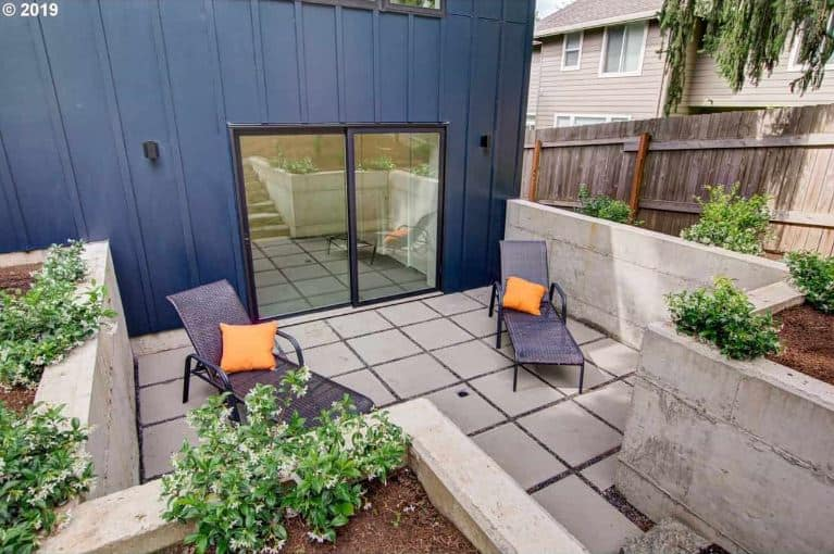 This is a small relaxation area at the back of the house accessed through glass sliding doors. It has gray concrete flooring and low walls that provide a view of the flowering shrubs planted by the edges that can be enjoyed on the couple of lounge chairs.